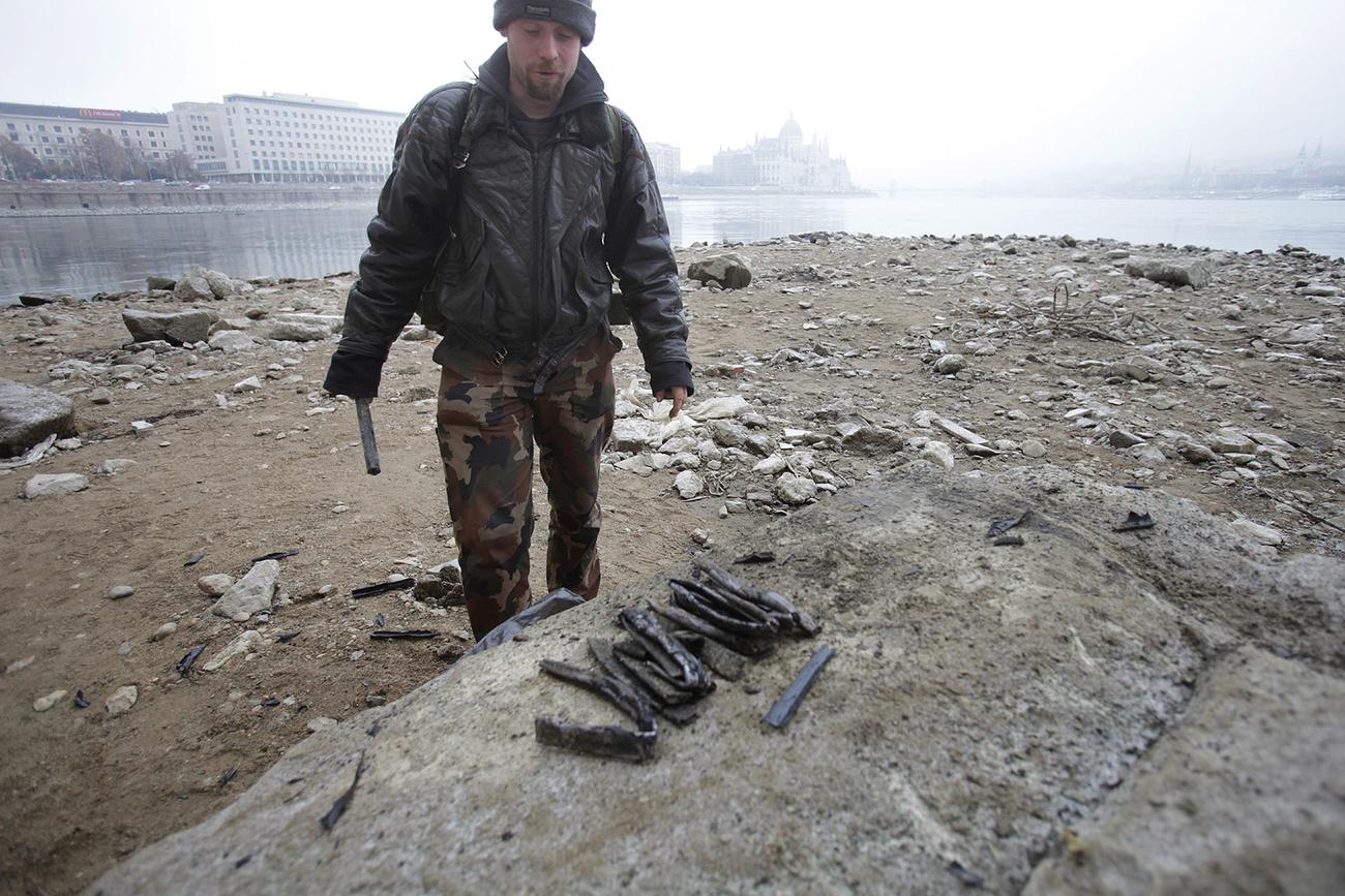 Egy fémgyűjtő a szárazra került fémhulladékot szedegeti.