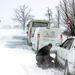 Kereket cserél és hóláncot rak fel az autójára egy férfi Tótvázsony és Nagyvázsony között