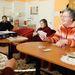 Asszonyok kártyáznak a kályha mellett a helyi idősek klubjában.