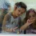 Gyermekek rajzolnak a helyi óvoda párás ablakára.