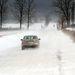 Egy személyautó halad a hófúvásban Hejce közelében.