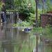 A Pap-sziget elöntött kis utcáján felborult kukát ringat a víz