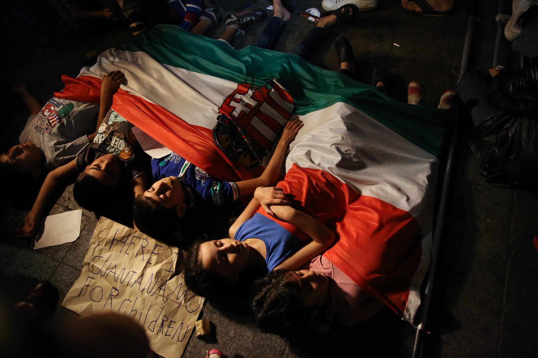 Gyerekek pihennek egy magyar zászlóval letakarva a Keletinél.