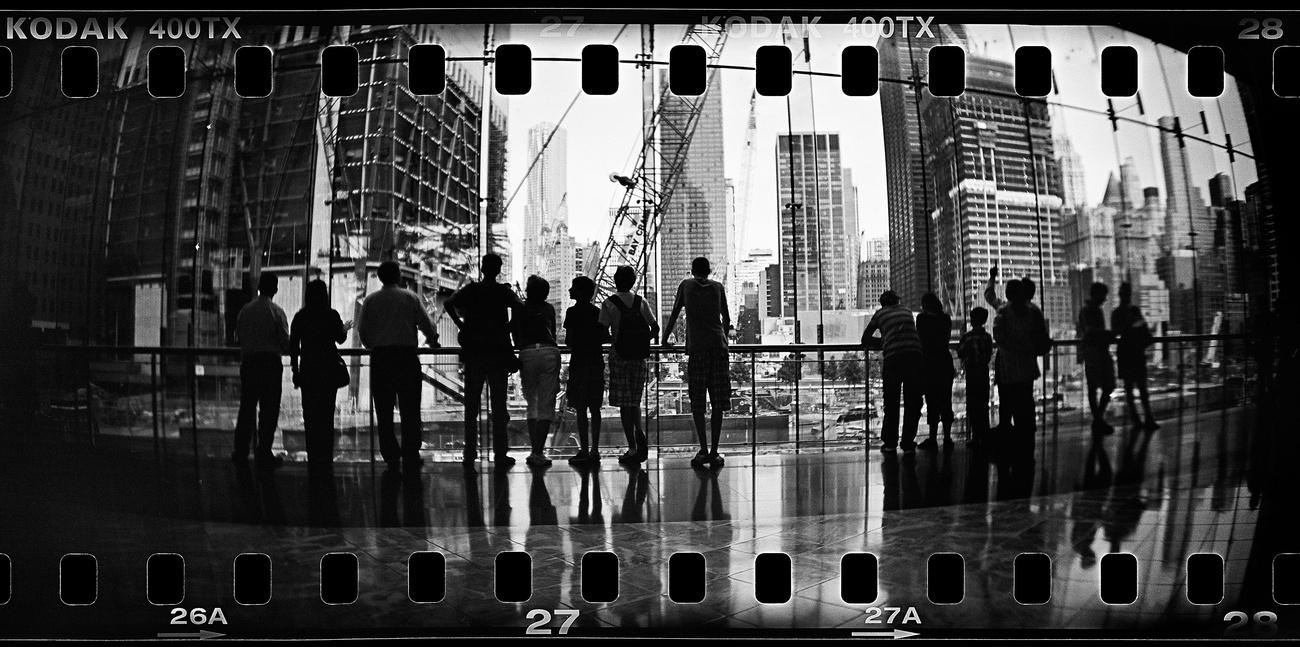 Egy ölelkező pár figyeli az újjáépülő Manhattant a Hudson-folyó partján pihenve.