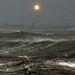 Viharos tenger New York egyik kikötőjében, a távolban a Cape May világítótorony fénye.
