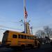 Félárbócra engedett zászló és üres iskolabusz az iskola mellett parkolóban