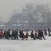 Vonatozó turisták a jégen a pekingi szmogban.