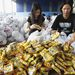 A Szociális és Jóléti Minisztérium  egyik raktárában önkéntesek élelmiszercsomagokat állítanak össze, amit a tájfun által leginkább területekre fognak kiszállítani.