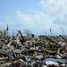 Esernyőt tart a kezében egy nő háza romjain, a vihar utáni első napokban. Az eddigi becslések szerint a vihar több mint egymillió otthont rombolt le és 4011 emberéletet követelt.  A környéken élő millióknak nemzetközi segélyszállítmányok jelentik az egyetlen reményt, míg a romok takarítása tart és az újjáépítés elkezdődik.