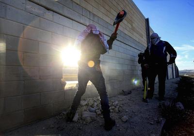 Palesztin aktivisták lyukat ütnek a ciszjordániai falon a berlini fal lebontásának évfordulóján.