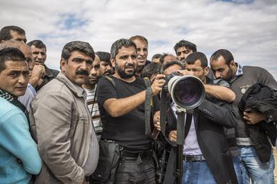 Bulent Kilic (középen) kurd menekülteknek mutatja a fotóit egy szíriai menekülttáborban.