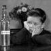 A kisfiú vágyakozva tekint az üvegre, amelyben a felirat szerint csukamájolaj van.
