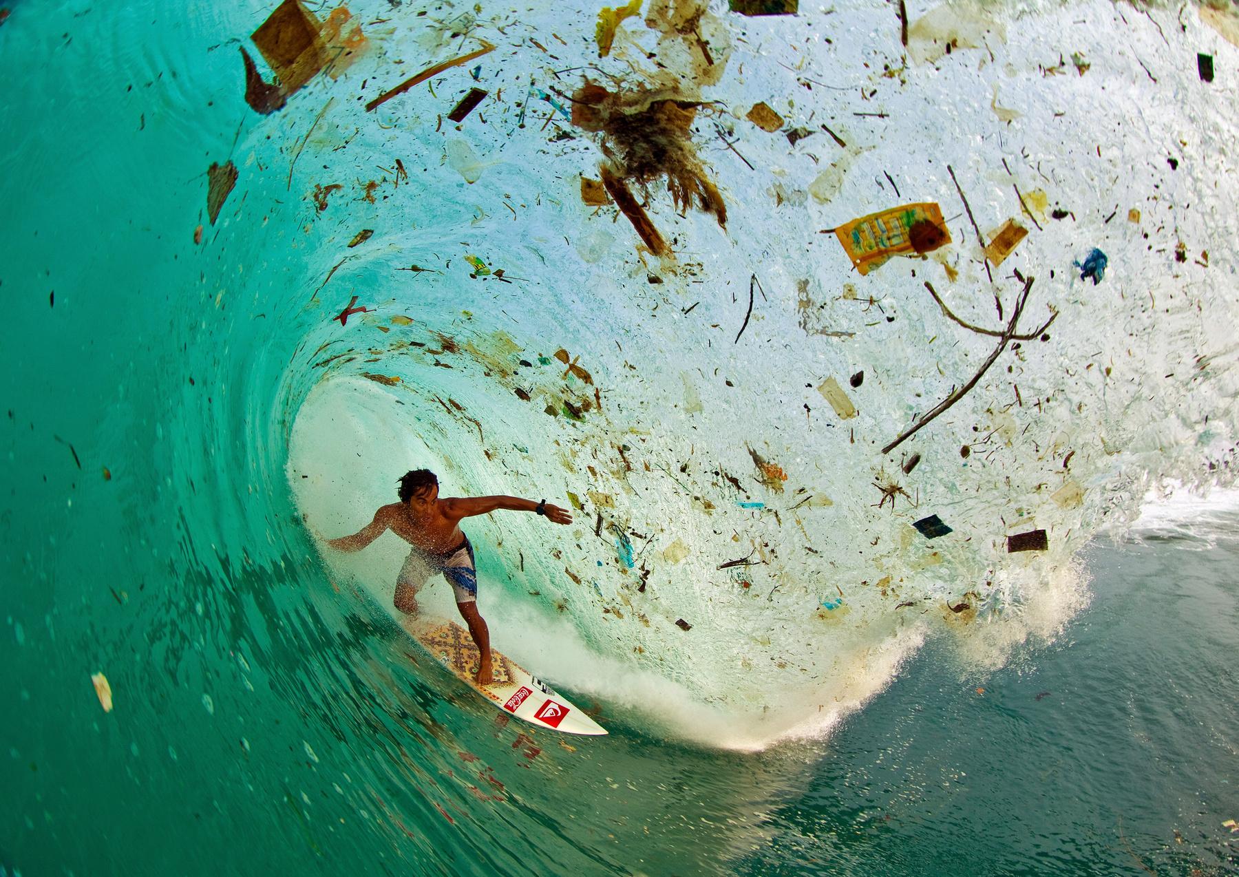 Hullámzó szemét között szörfözik egy férfi Indonéziában.