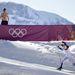 Félmeztelen férfi nézi a svéd Charlotte Kallát, aki a 2014-es szocsi téli olimpia 10 kilométeres női klasszikus stílusú sífutásában versenyez