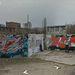 Grafitis éppen festi a falat, a kép bal oldalán láthatjuk a fesékesflakonokat is.