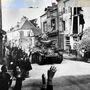 Francia páncélosalakulat halad át St. Mere Eglise városának főutcáján a D-napon, a város lakói integetve üdvözlik őket.