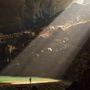 Egy barlangász körvonala a betűző nap fényénél.